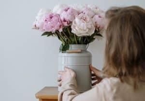mujer colocando jarron de flores frescas